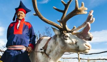 A local man in traditional norwegian dress and his reindeer