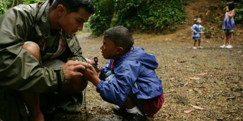 A guide shows a young boy how to use a compass in the rainforests of Belize