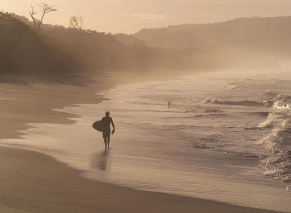 A surfer walks the coastline after a day in the surf