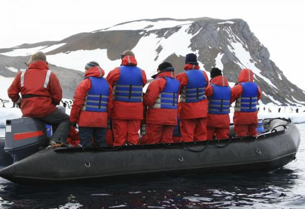 A group of travellers sail around a penguin colony off the shores of Antarctica