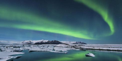 The northern lights dance over the Arctic landscape