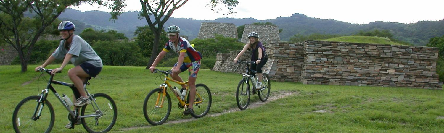 Several travelers bike through ruins of Guatemala