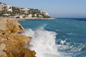 Waves crash against the beaches of Nice, France