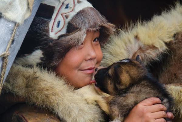 A Chukchi child holds a pup