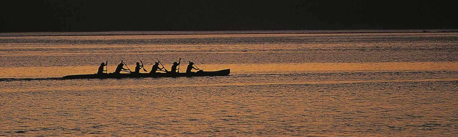 Locals paddle a traditional canoe at sunset