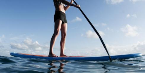 A young woman explores via Stand Up Paddleboard (SUP)
