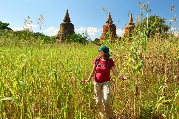 A backpacker walking and looking across field to ancient buddhist stupas
